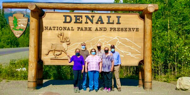 A group of 6 people wearing masking in front of the Denali National Park sign